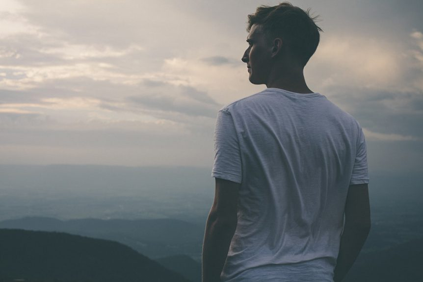 man looking at sunset on mountain